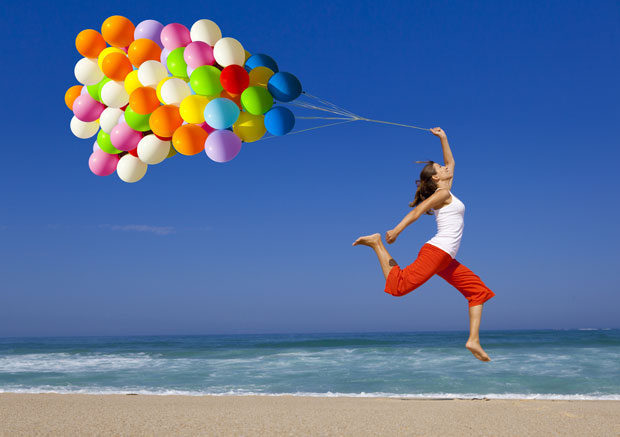 Jumping with helium balloons on beach