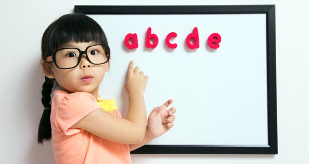 Girl learning her alphabet on white board
